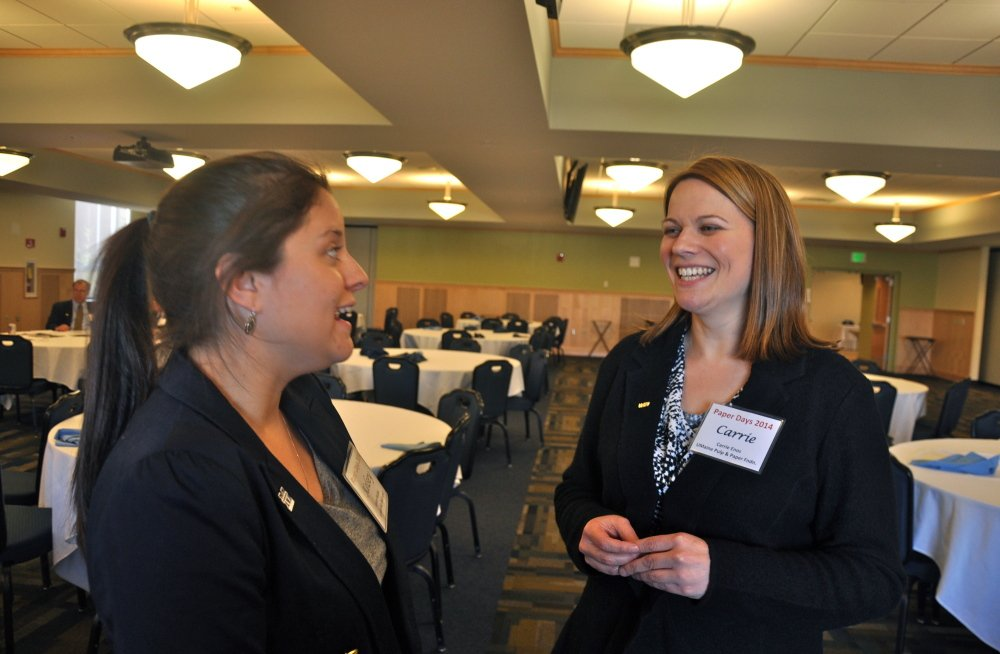 Kelsey Bolduc, left, a chemical engineering student at the University of Maine, tells Carrie Enos, president of the Maine Pulp and Paper Foundation, about her decision to pursue a career in the paper industry rather than the legal field.