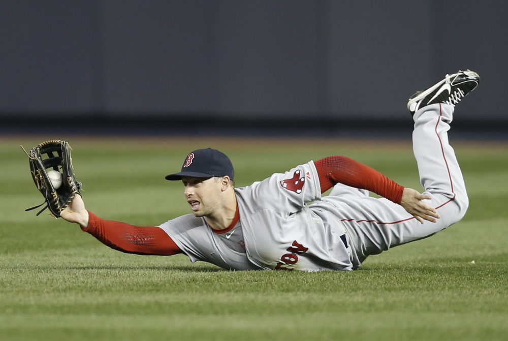 Boston Red Sox right fielder Daniel Nava shows the ball to the umpire after making a sliding catch on a third-inning fly-out hit by Yankees third baseman Yangervis Solarte.