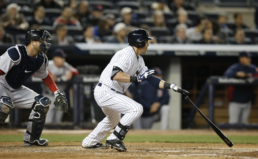 New York Yankees' Jacoby Ellsbury, right, hits a fifth-inning RBI-double in Thursday's game against the Boston Red Sox at Yankee Stadium in New York.