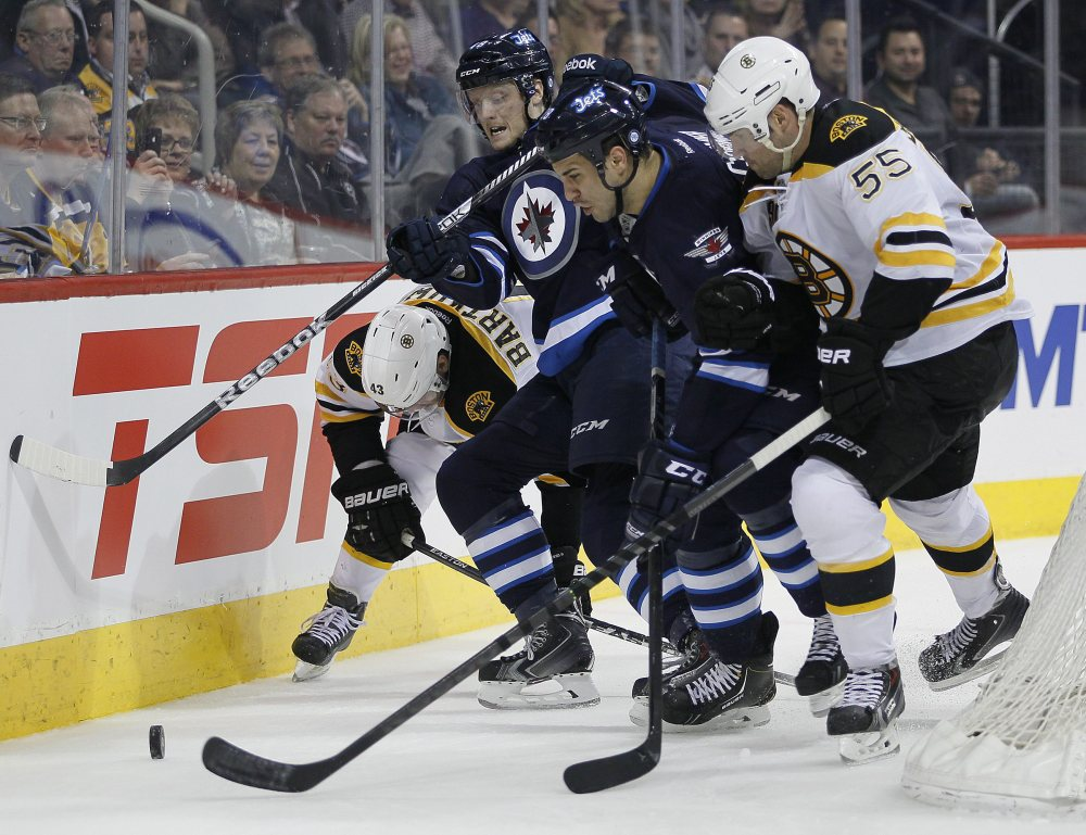 Boston Bruins' Matt Bartkowski and Johnny Boychuk (55) scramble with Winnipeg Jets' Carl Klingberg, center left, and Patrice Cormier for the puck behind the Bruins' net during the second period Thursday.