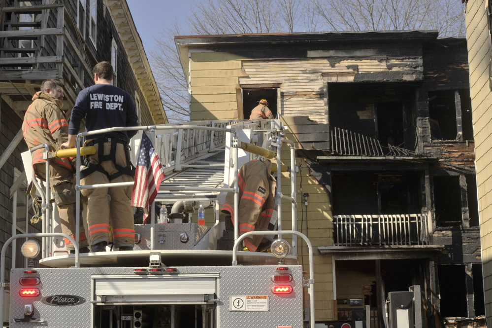Lewiston firefighters work Thursday to clear the scene of an apartment building fire on Howe Street in Lewiston that left several dozen people homeless.