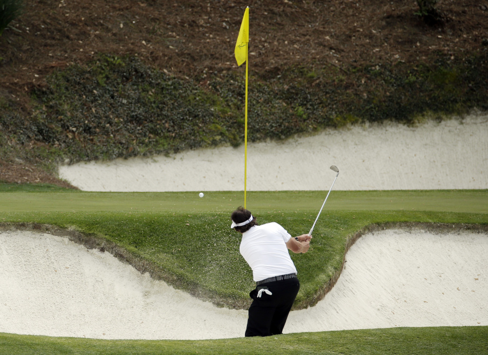 Phil Mickelson hits out of a bunker on the 12th hole during the second round of the Masters golf tournament Friday, April 11, 2014, in Augusta, Ga.