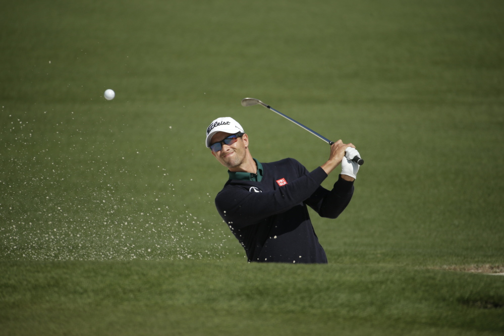 Adam Scott of Australia hits out of a bunker on the second fairway during the first round of the Masters golf tournament Thursday in Augusta, Ga. He's the defending champion.