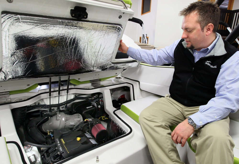 Jeremy Moore of SkipperBud's looks over the jet drive engine on a Scarab 195 impulse. Boats that use a jet drive instead of a propeller are becoming more popular, the boat dealer says.