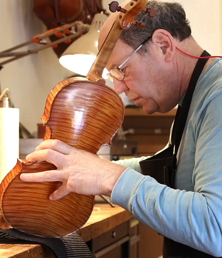 In his Portland workshop, Jonathan Cooper repairs an instrument owned by violinist Mark O'Connor.
