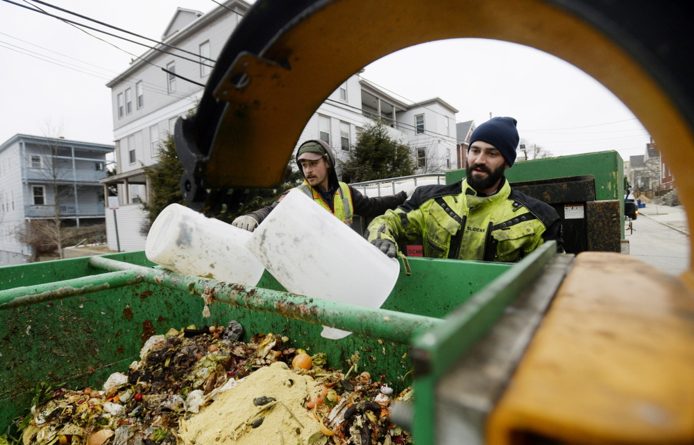 Lee Michael, left, and Cory Fletcher of Garbage to Garden pick up kitchen scraps during their rounds in Portland late last month. The waste will be composted.