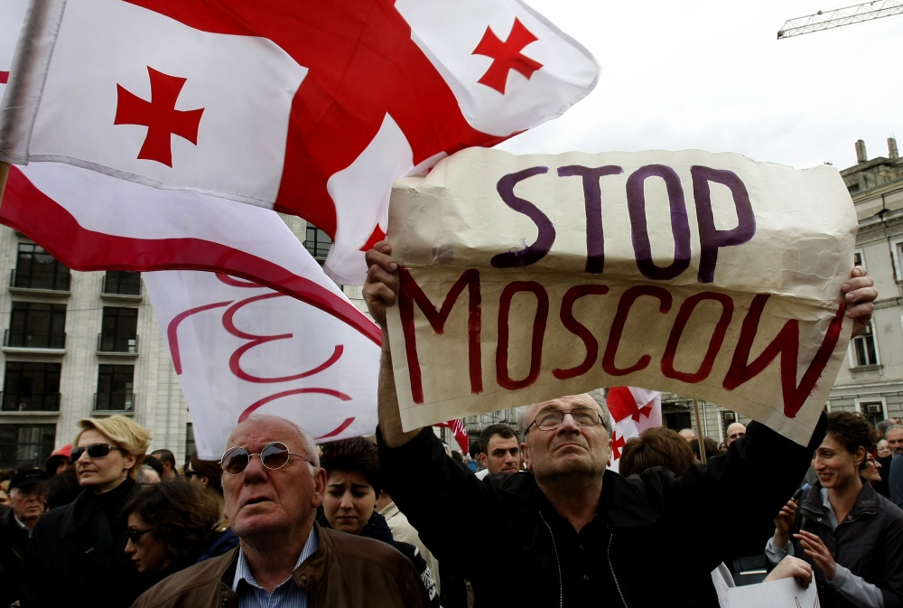 Demonstrators hold a Georgian national flag and a poster during a rally in support of Ukraine in Tbilisi, Georgia, on Sunday.
