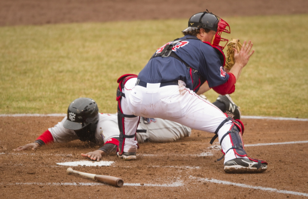 Sea Dogs catcher Matt Spring waits for the late throw as New Britain's Corey Wimberly slides safely into home in the fifth inning Sunday at Hadlock Field. New Britain avoided a four-game series sweep, earning a 6-3 win.