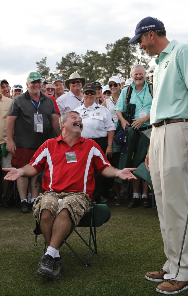 Matt Kuchar gets his golf ball from Ricky Earl after it landed on Earl's lap on the 18th hole in the final round of the Masters on Sunday.