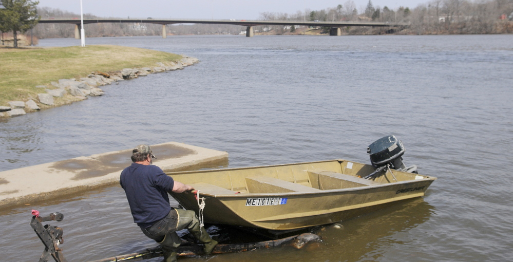 "Kevin Lemar of Belfast hitches his vessel to a trailer Monday at the boat landing on the Kennebec River in Gardiner. Lemar, who was fishing for suckers, said conditions on the Kennebec were unpredictable. ""Year after year, it's always different,"" Lemar said."