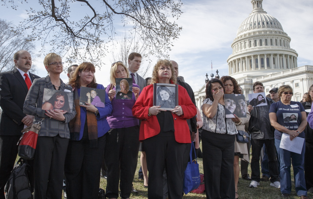 Family members of those who died in General Motors cars with safety defects hold photos of them April 1 outside the U.S. Capitol in Washington. A U.S. House committee is investigating GM's recall of cars with faulty ignition switches.