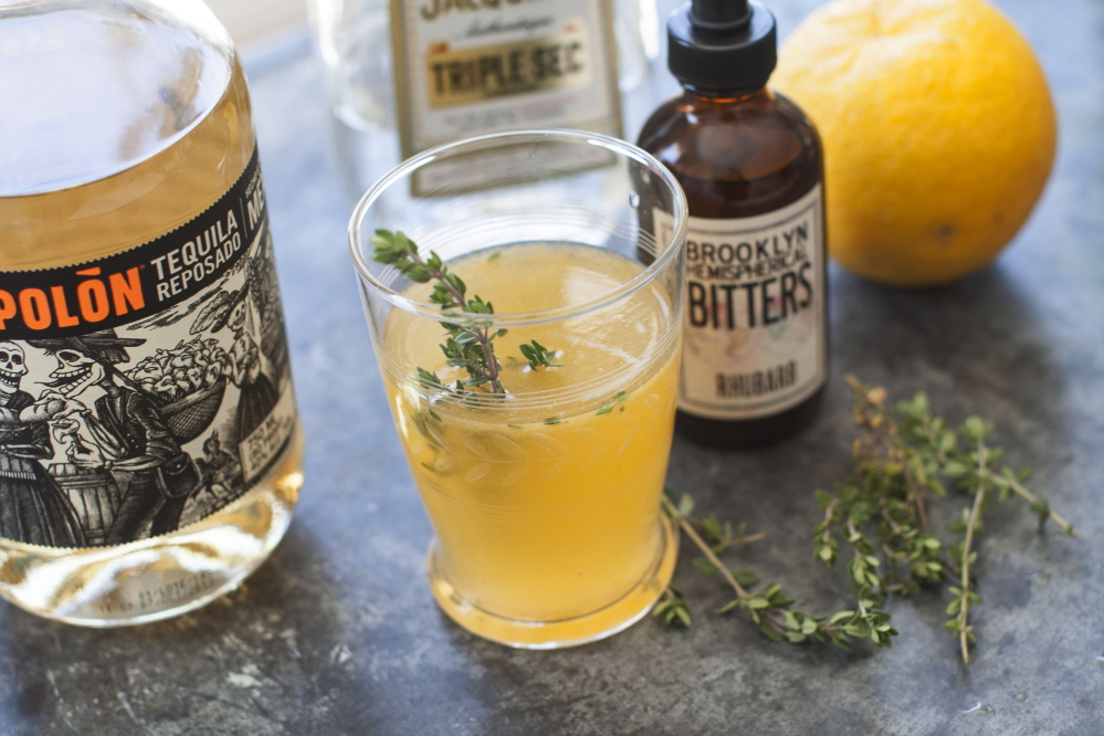 A Summer Rain, made with rhubarb bitters, tequila and orange liqueur, is topped off with a sprig of fresh thyme.