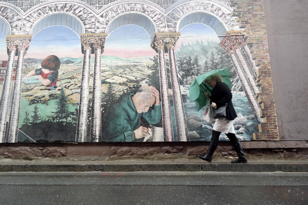 A woman takes shelter under her umbrella as she walks past a mural in Pittsfield, Mass., on Tuesday.