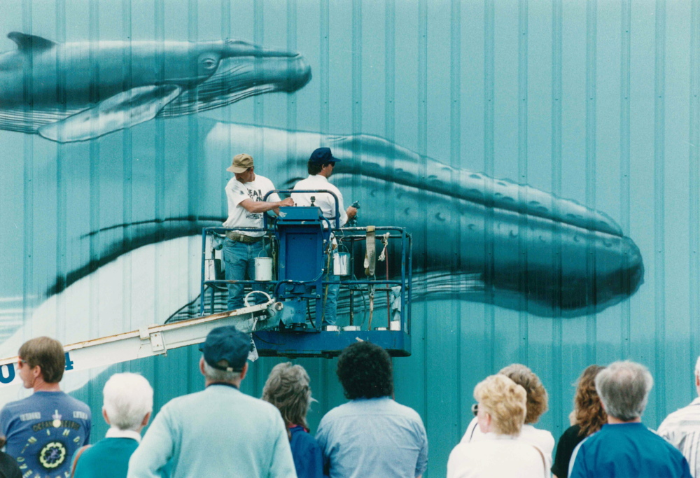 Artist Robert Wyland, known simply as Wyland, and an assistant work on the whale mural at the Maine State Pier in Portland in June 1993. The local artwork was the first of 17 marine-themed murals the artist created in 17 East Coast cities that year