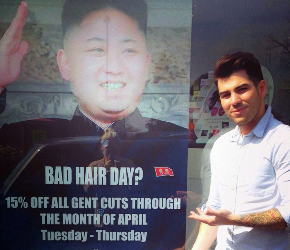 At M&M Hair Academy in South Ealing, London, barber Karim Nabbach stands next to a poster poking fun at North Korean leader Kim Jong Un's hairstyle.