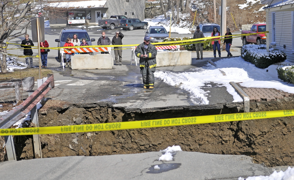 A firefighter stands at the edge of the washed-out connector street between Main and Water streets Wednesday in downtown Dexter.