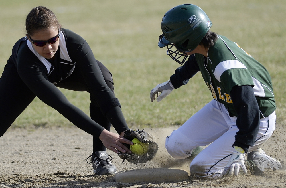 Kim Fisher of McAuley steals second base, sliding in ahead of a late tag applied by Kaylah Abdul of Marshwood during their season-opening softball game Thursday in Portland. Marshwood won in 13 innings, 7-5.
