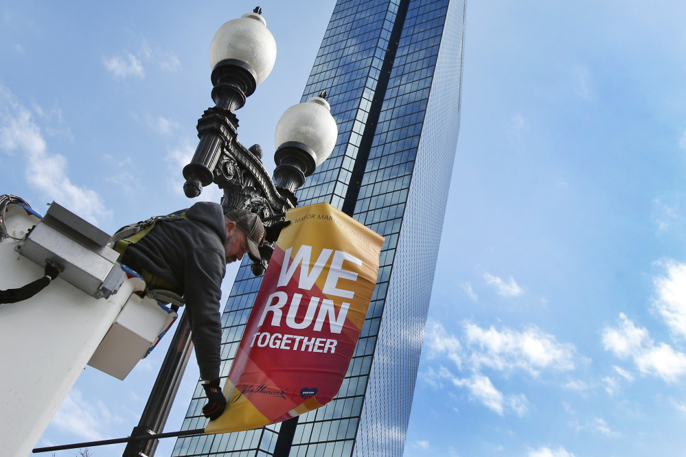 Charlie McCarthy hangs a banner in March announcing the Boston Marathon on a lamppost along Boylston Street in Boston. More runners and more visitors than ever are expected in Boston for the marathon.