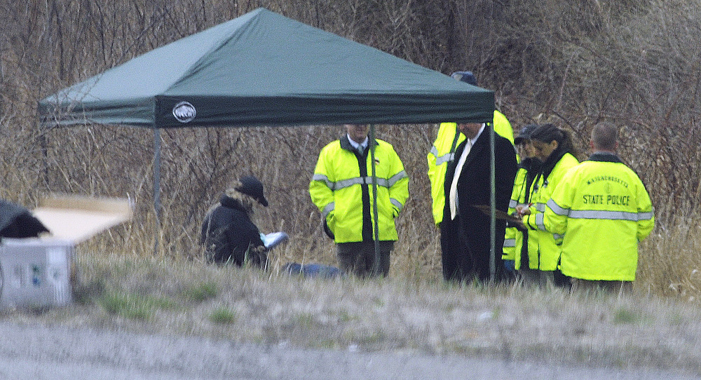 Massachusetts State Police stand along Interstate 190 near Sterling, where a child's body was found Friday. Jeremiah Oliver of Fitchburg has been missing since September.