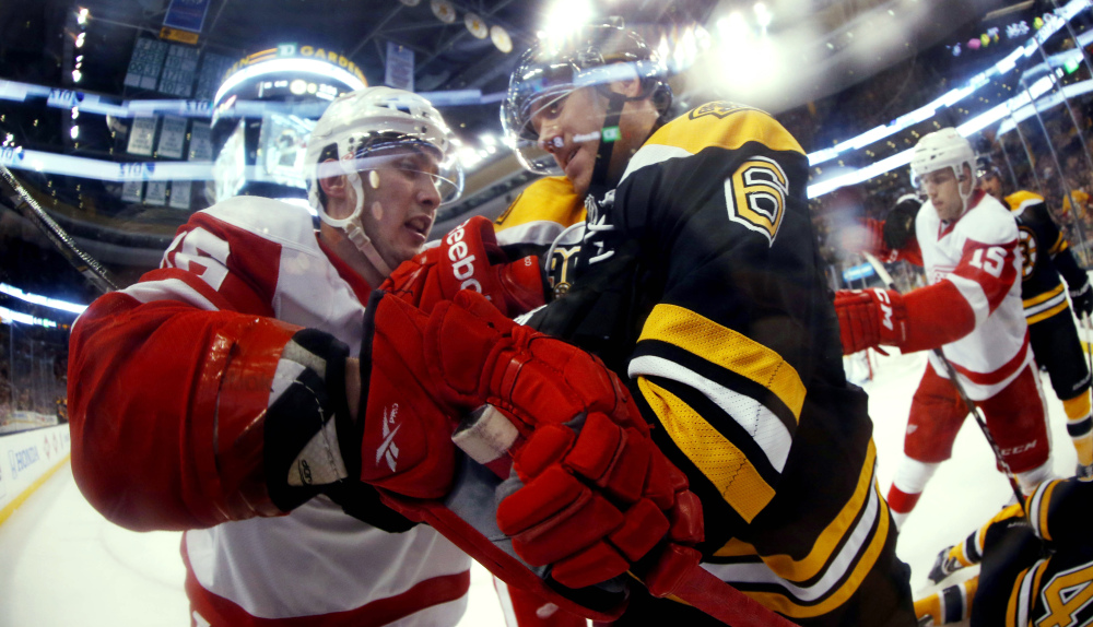 In this photo taken with a fish eye lens, Boston Bruins defenseman Corey Potter (6) struggles with Detroit Red Wings' Riley Sheahan during the first period of a first-round NHL playoff hockey game in Boston on Friday, April 18, 2014.