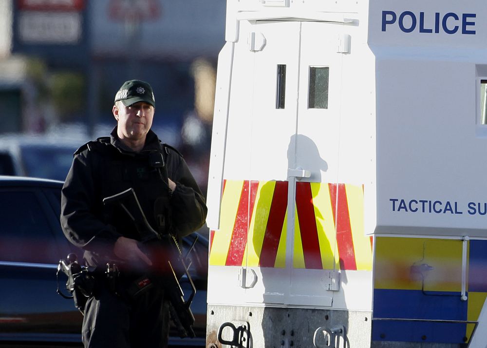 A police officer patrols the area close to where Tommy Crossan, a senior Irish Republican Army hard-liner, was shot dead Friday in Belfast, Northern Ireland.