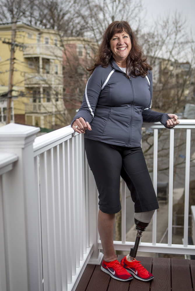 Karen McWatters poses for a portrait at her home in Somerville, Mass. Being injured in the Boston Marathon bombings last year has led to many changes in her life. She and her husband have purchased a Portland condo adapted for her needs, and the couple is helping a teen who lost a leg in an accident. McWatters misses pre-bombing anonymity, but feels that with her visibility as a survivor comes power to help others.