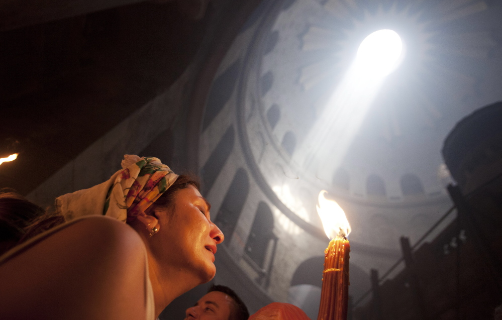 A Christian pilgrim holds candles at the church of the Holy Sepulcher, traditionally believed to be the burial site of Jesus Christ, during the ceremony of the Holy Fire in Jerusalem's Old City Saturday.