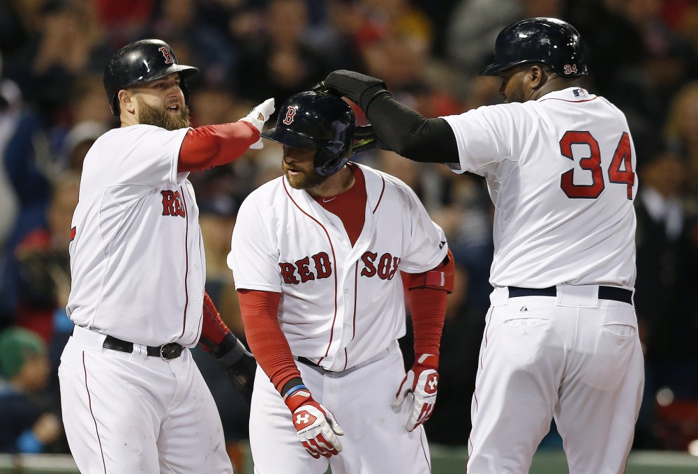 David Ortiz, right, and Mike Napoli, left, of the Red Sox celebrate after scoring a on a three-run homer by Jonny Gomes, center, in the sixth inning of Sunday's game against the Orioles. Gomes' shot started Boston's comeback from a 5-0 deficit.