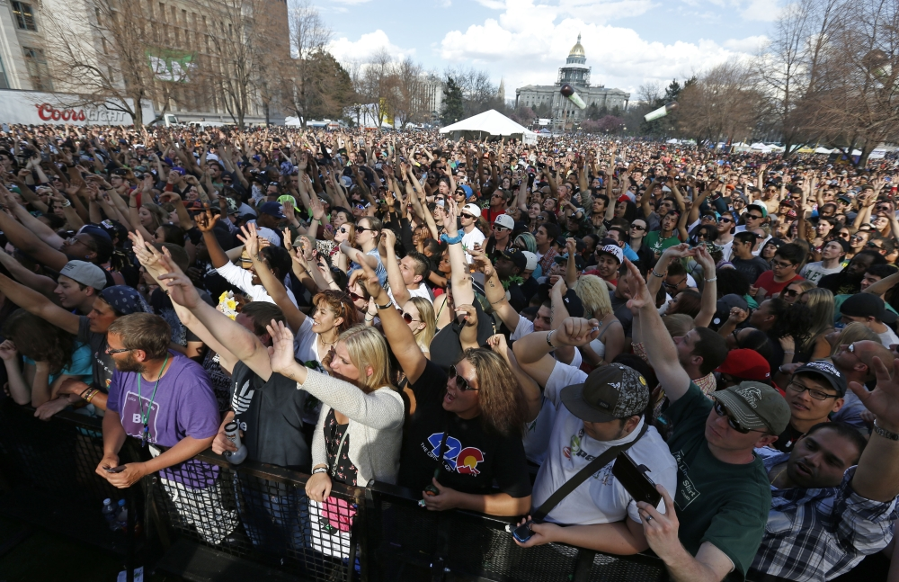 Partygoers listen to live music on the second of two days at the annual 4/20 marijuana festival in Denver, Sunday.