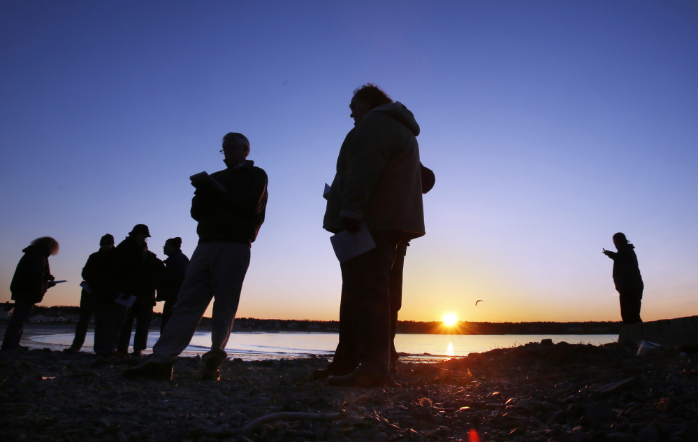 The Rev. Charles Whiston, fifth from left, of the South Congregational Church in Kennebunkport, recites a prayer during an ecumenical Easter sunrise service at Kennebunk Beach on Sunday.