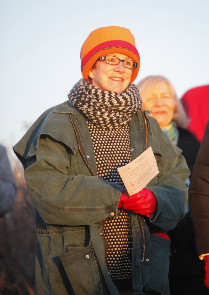 Cindy Connelly of Kennebunkport listens to a closing prayer during an ecumenical Easter sunrise service at Kennebunk Beach on Sunday.