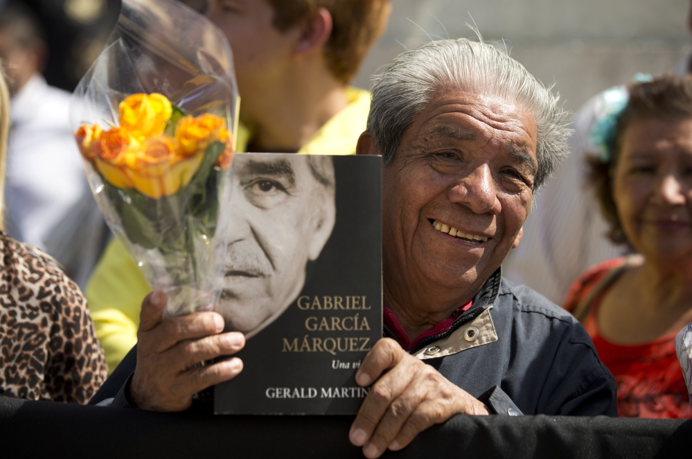 A well-wisher holds an autobiography of Colombian Nobel laureate Gabriel Garcia Marquez as he waits outside the Palace of Fine Arts in Mexico City on Monday.