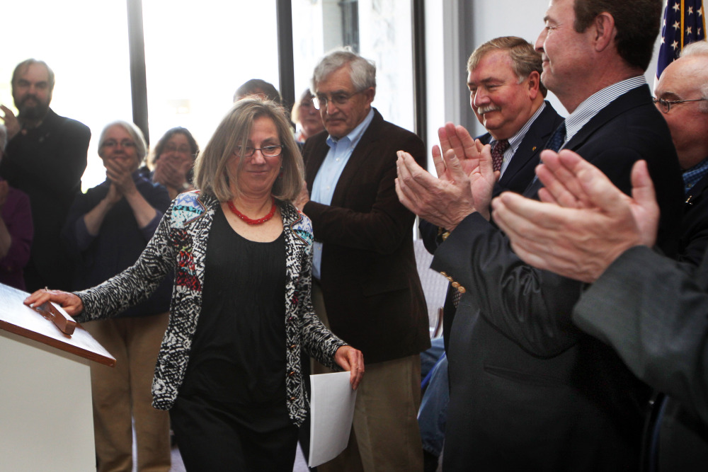 New Hampshire's first Democratic House speaker in 84 years, Terie Norelli, center, is applauded by supporters following a news conference Monday in Concord, N.H.