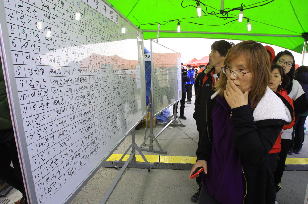 A relative of a passenger aboard the sunken ferry Sewol reads the official list of the dead, in Jindo, South Korea, on Monday. Anguish has turned to fury for some family members and people across the nation.
