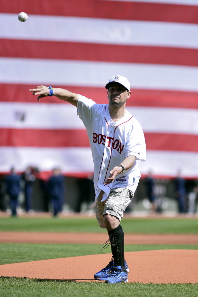 Though still suffering the effects of last year's bombing, Marc Fucarile throws out the ceremonial first pitch before Monday's game at Fenway Park.