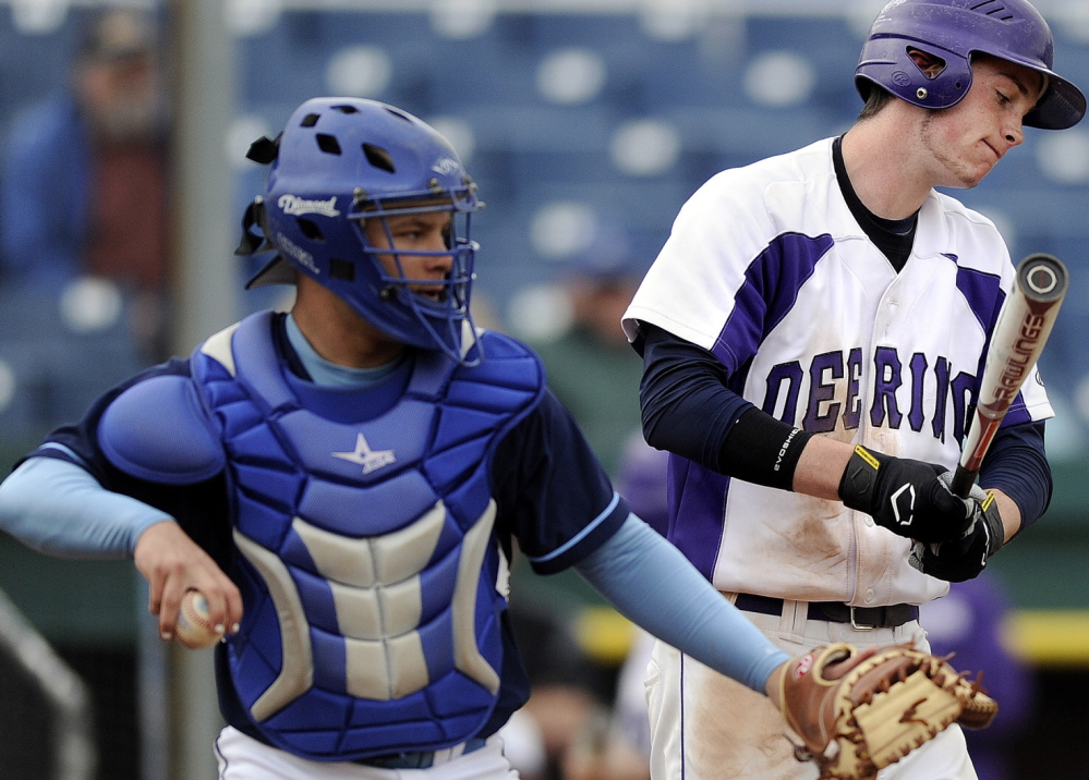 Westbrook catcher Kyle Heath prepares to throw the ball around the horn as Nick Carmichael of Deering reacts after striking out at Hadlock Field. Westbrook is seeking a second straight state title and Deering is attempting to work its way back into contention.