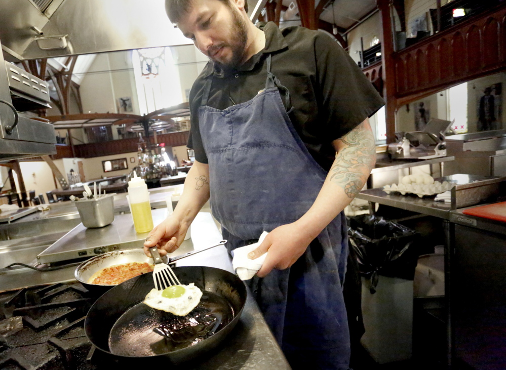 Executive chef Pete Sueltenfuss of Grace in Portland fries a duck egg to top a pizza.