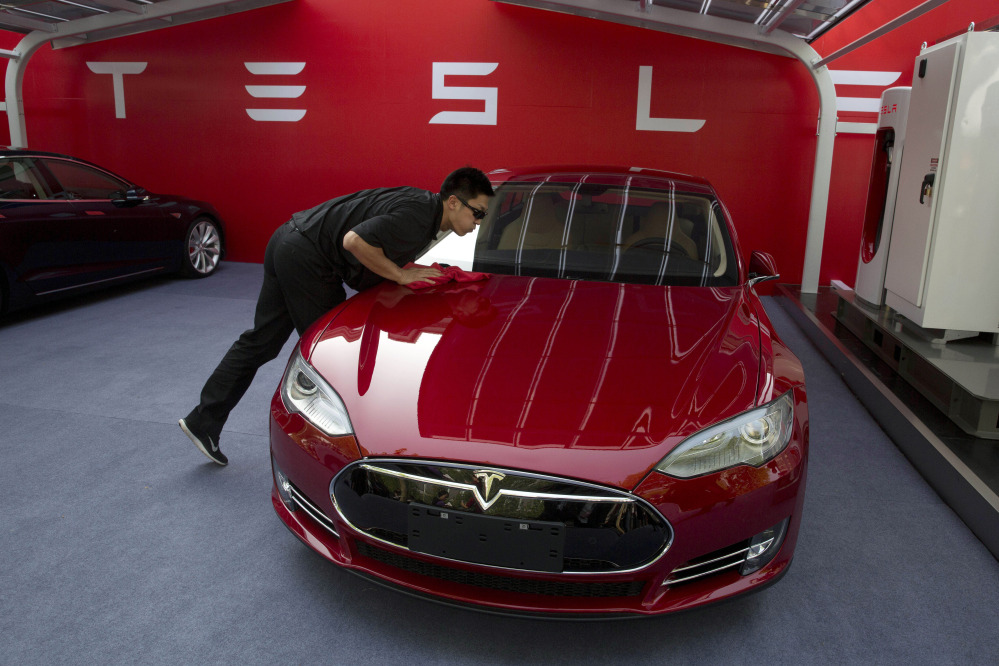 A worker cleans a Tesla Model S sedan before an event to deliver the first set of cars to customers in Beijing on Tuesday. CEO Elon Musk said the company will build a nationwide network of charging stations and service centers as fast as it can.