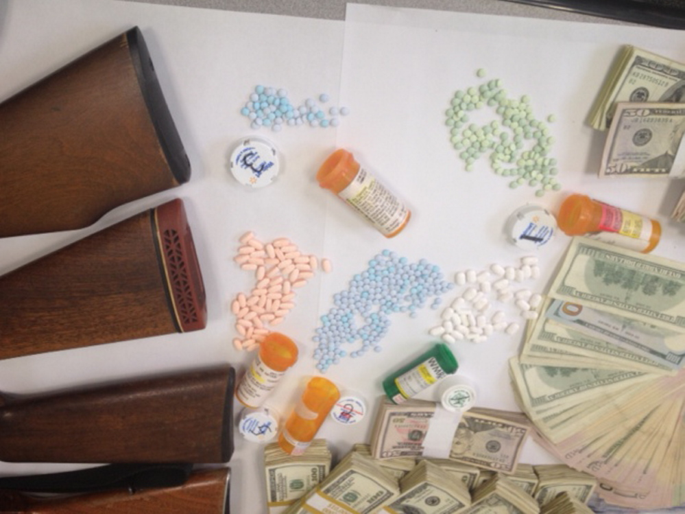 Weapons, pills and cash seized in an Avon drug bust are displayed at the Franklin County Sheriff's Office on Tuesday.