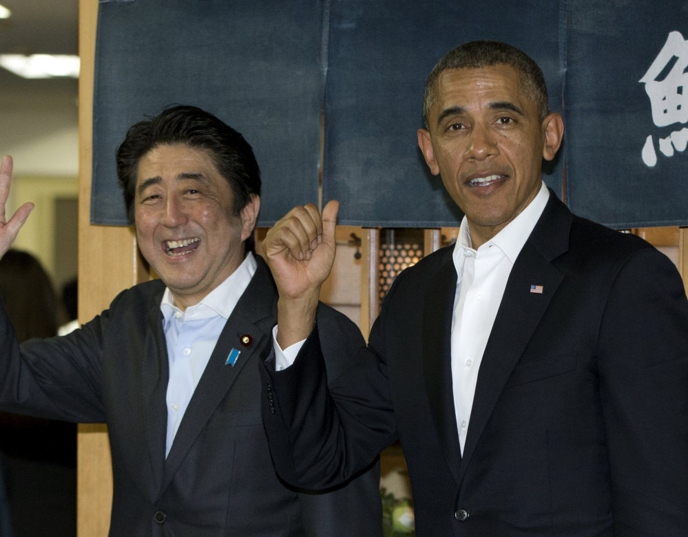 President Obama and Japanese Prime Minister Shinzo Abe leave a sushi restaurant in Tokyo Wednesday.