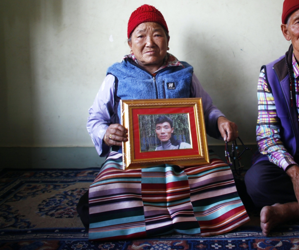 In Katmandu, Nepal, on Wednesday, Nimdige Sherpa holds a portrait of her son – avalanche victim Ang Kaji Sherpa – with her husband Ankchu Sherpa at her side.
