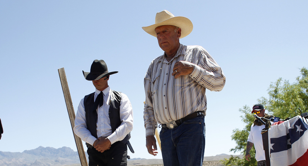 Rancher Cliven Bundy, in light hat, who has resisted government efforts to round up his cattle, walks offstage Thursday after speaking at a news conference near Bunkerville, Nev.