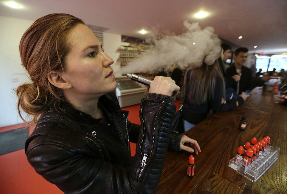 Talia Eisenberg, co-founder of the Henley Vaporium, uses her vaping device in New York on Feb. 20. Soon, the Food and Drug Administration will propose rules for e-cigarettes. The rules will likely have big implications for a fast-growing industry and its legions of customers.