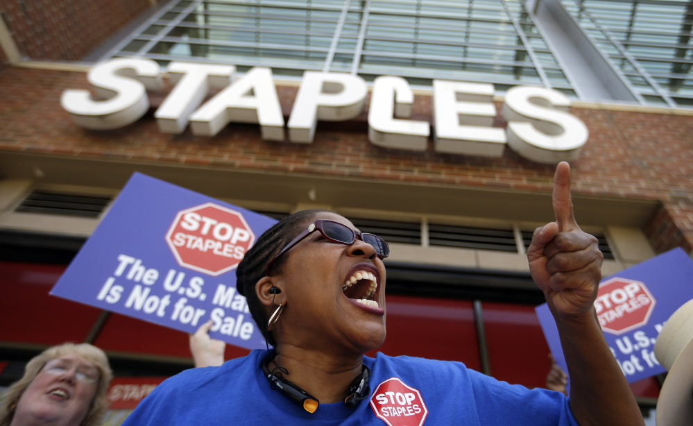 U.S. Post Office employee Detra Parker chants Thursday during a protest outside a Staples store in Atlanta. Thousands of postal workers picketed outside Staples stores nationwide Thursday to protest a pilot program that allows the office supply chain to handle U.S. mail.
