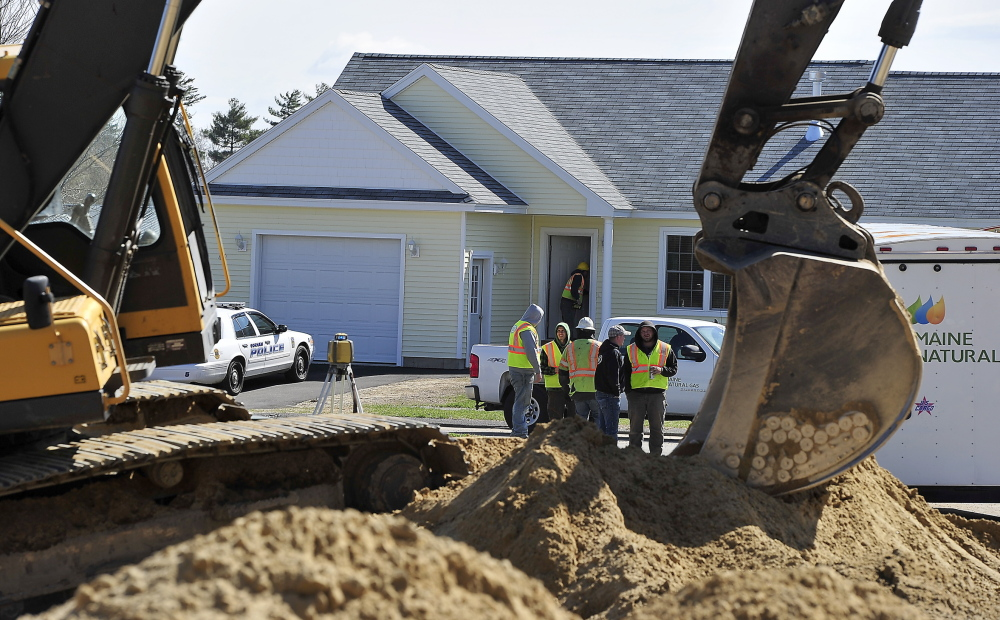 Maine Natural Gas employees discuss the accident with construction workers as others go door to door evacuating residents and checking empty houses for gas levels after a gas main break caused by this excavator happened at Hawkes Farm development on Tink Drive in Gorham.