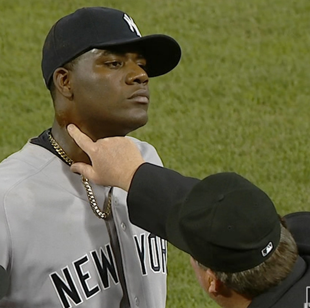 An umpire finds pine tar on Yankees pitcher Michael Pineda's neck just before ejecting him from the game Wednesday.
