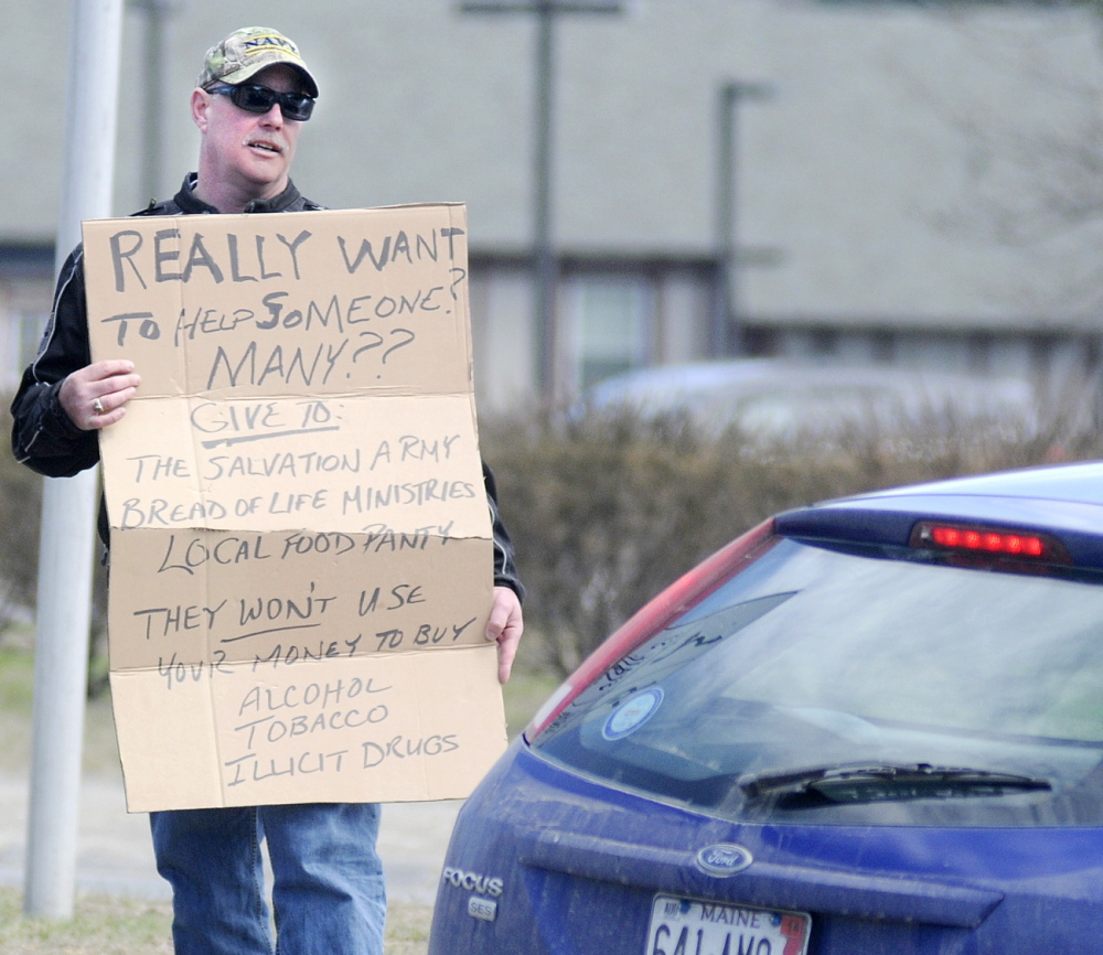 Augusta Police Chief Robert Gregoire speaks with a driver Friday while carrying a sign that discourages motorists from giving money to panhandlers at Memorial Circle.