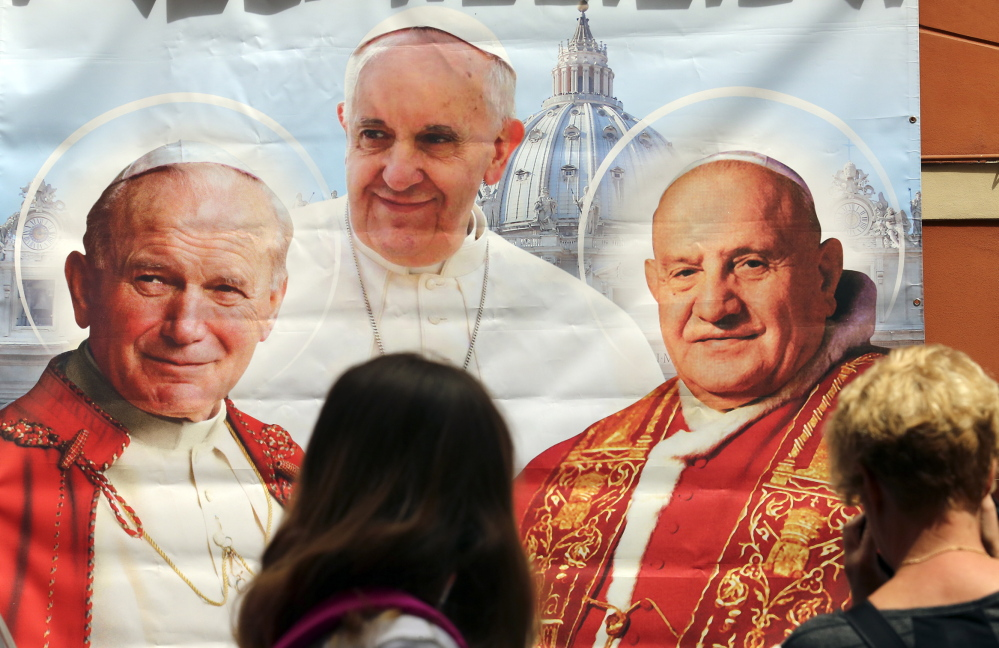 A woman takes a picture of an illustration depicting popes John Paul II, from left, Francis and John XXIII outside a shop in Rome on Thursday. Pope Francis will canonize John Paul II and John XXIII on Sunday.