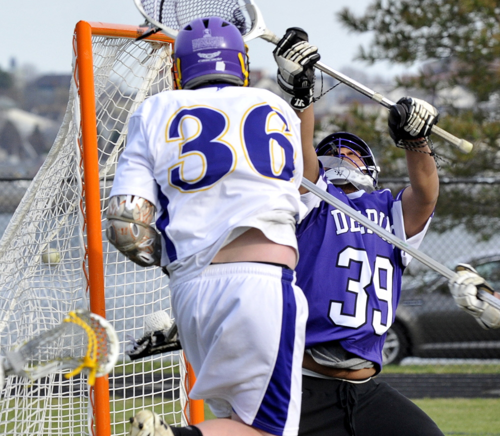 Frank Curran of Cheverus finds enough room to send the ball past Deering goalkeeper Lenny Sarem during their SMAA lacrosse game Friday at Cheverus High. Cheverus improved to 1-1 with a 17-7 victory in Deering's opening game.