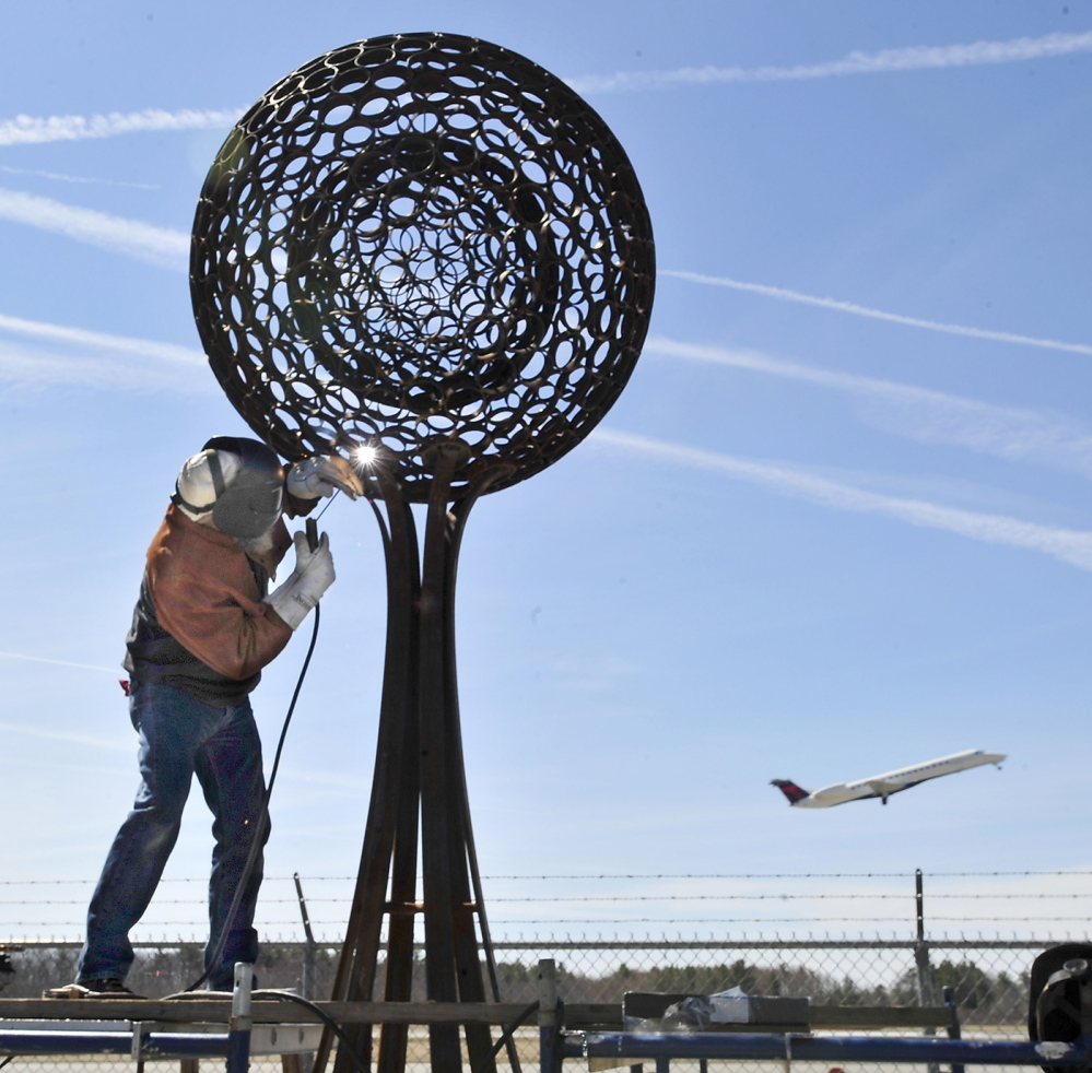 """Sculptor Jay Sawyer of Warren installs """"A Spirit of Its Own"""" on the Jetport Access Road on Friday."""